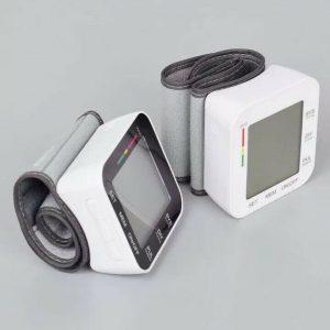 Two wrist blood pressure monitors, one white, one black